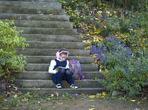 Girl with a book sitting on the steps. Girl reading a book sitting on the steps in the park royalty free stock photography