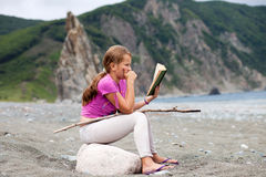 Girl reading book sitting on a stone on a sandy sea shore Royalty Free Stock Photos