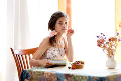 Girl reading book sitting at table with strawberry Royalty Free Stock Photography