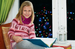Girl reading a book sitting on the window on Christmas Eve Stock Image