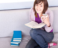 Girl reading a book on sofa Stock Photos