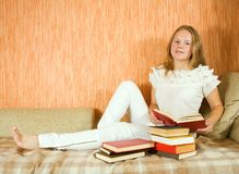Girl reading book on sofa Stock Image
