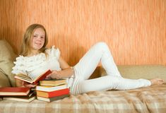 Girl reading book on sofa Royalty Free Stock Image