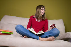 Girl reading book on sofa Royalty Free Stock Photography