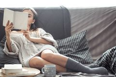 Girl reading book on sofa. Beautiful girl reading a book on the sofa in the cozy interior , the concept of comfort and read Stock Photo