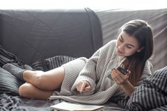Girl reading book on sofa. Beautiful girl reading a book on the sofa in the cozy interior , the concept of comfort and read Royalty Free Stock Image