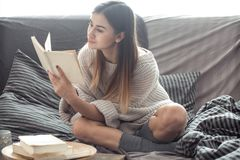 Girl reading book on sofa. Beautiful girl reading a book on the sofa in the cozy interior , the concept of comfort and read Royalty Free Stock Photo