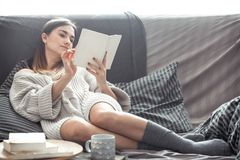 Girl reading book on sofa. Beautiful girl reading a book on the sofa in the cozy interior , the concept of comfort and read Stock Images