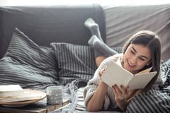 Girl reading book on sofa. Beautiful girl reading a book on the sofa in the cozy interior , the concept of comfort and read Stock Image