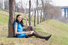 Girl reading book in spring park Royalty Free Stock Photo