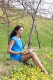 Girl reading book in spring park Royalty Free Stock Photos