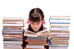 Girl reading a book among stacks of books Royalty Free Stock Photos