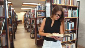 Girl reading a book standing in the library stock footage