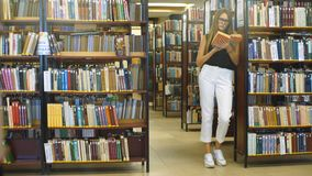 Girl reading a book standing in the library stock video