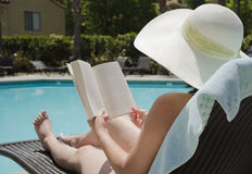 Girl reading a book. Girl in a summer heat reading a book by the swimming pool Royalty Free Stock Photos
