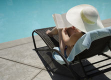 Girl reading a book. Girl in a summer heat reading a book by the swimming pool Stock Photography