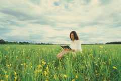 Girl reading a book on summer wildflower meadow Stock Photo
