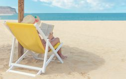 Girl reading a book in sun chair at the beach royalty free stock photography