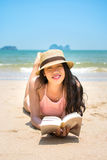 Girl reading book and sunbathing on the beach Stock Photo