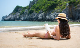 Girl reading book and sunbathing on the beach Royalty Free Stock Image