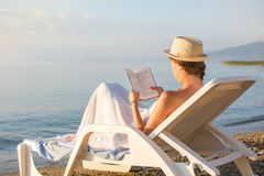 Girl reading a book in sunbed Royalty Free Stock Photo