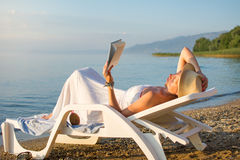 Girl reading a book in sunbed Royalty Free Stock Photos
