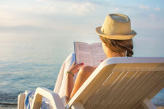 Girl reading a book in sunbed. At the beach Stock Image