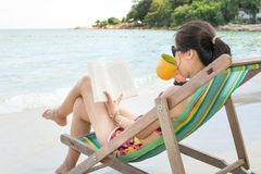 Girl reading a book in sunbed by the sea Stock Images