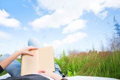 Girl reading book. Sunny morning. Green grass royalty free stock photography