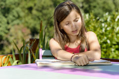 A girl reading a book, on a table, Stock Image