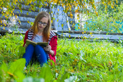 Girl reading a book. Teenager girl in red jacket and blue jeans sitting in autumn forest and reading a book royalty free stock photos