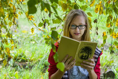 Girl reading a book. Girl teenager in red jacket reading Turgenev book in autumn forest royalty free stock photography