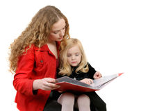 Girl reading book to sister Royalty Free Stock Photography