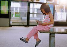 A girl reading a book at a train station royalty free stock photos