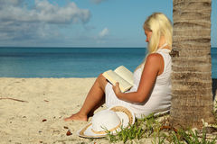 Girl reading book at tropical beach Stock Photo