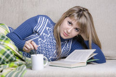 Girl reading a book under a blanket on the couch, and with a Cup of tea Royalty Free Stock Image