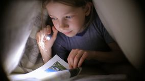Brother and sister read a book under a blanket with a flashlight in little girl is reading a book under a blanket with a flashlight in a dark room sciox Gallery