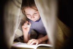 Little girl is reading a book under a blanket with a flashlight in a dark room at night Stock Image