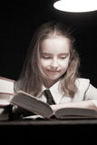 Girl reading book under lamp Stock Images