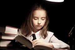 Girl reading book under lamp Royalty Free Stock Photos