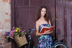 Girl reading the book with a vintage bicycle and a basket of flo Royalty Free Stock Image