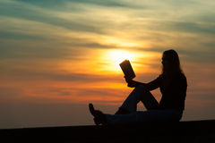 Girl reading a book on the wall at sunset. In silhouette Royalty Free Stock Photo