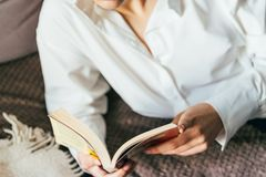Girl reading a book in a warm blanket. woman lies, lay down on the bed, a blanket, a sofa, a couch and holds a book. Girl reading Stock Photos