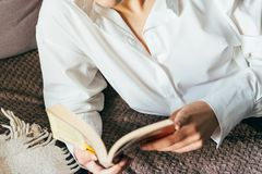 Girl reading a book in a warm blanket. woman lies, lay down on the bed, a blanket, a sofa, a couch and holds a book. Girl reading Stock Image