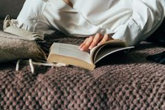 Girl reading a book in a warm blanket. woman lies, lay down on the bed, a blanket, a sofa, a couch and holds a book. Girl reading Royalty Free Stock Photography
