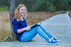 Girl reading book on wooden path in forest Royalty Free Stock Photos