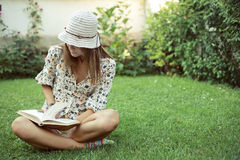 Girl reading book in yard Royalty Free Stock Images