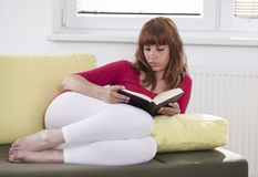 Girl reading a book. A young woman is reading a book laying on the sofa, relaxing Stock Images