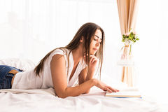 Girl reading books on the bed at home Stock Image