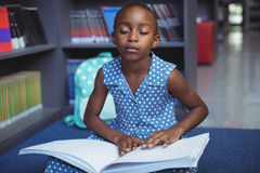 Girl reading braille book in library. Girl reading braille book while sitting in library Royalty Free Stock Images